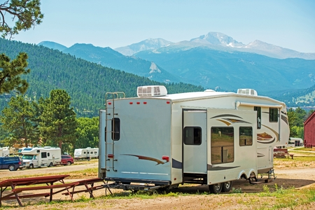 trailer: RV Fifth Wheel Camping. Travel Trailer with Extended Sliders in the Mountain Campground.