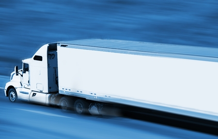 trailer: Speeding Semi Truck on the Highway. Blue Color Grading with Motion Blur. Transport and Logistics Concept. Stock Photo