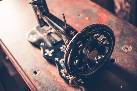machine made: Vintage Iron Made Sewing Machine on Aged Wooden Desk.Vintage Technology Stock Photo