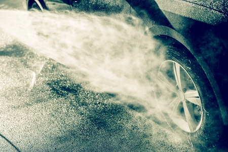 soaping: Alloy Wheel Cleaning Using High Pressure Water. Car Wash Cleaning. Stock Photo