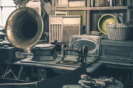 Inventário de lojas de antiguidades. Velho gramofone, máquina de costura e outras coisas do início do século XX. Foto de archivo
