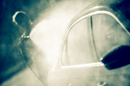 Woman Cleaning Modern Car Using High Pressure Water Sprayer. photo