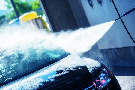 soaping: Hand Car Wash Cleaning. Bluish Color Grading. Cleaning Modern Compact Car. Stock Photo