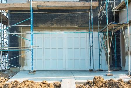 residential garage: Garage Door Construction. New Residential House Construction Closeup on the Garage Doors and Scaffolding. Residential Area Development.
