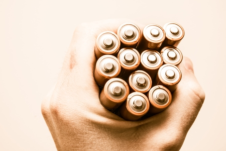 Batteries in the Hand. Mobile Power Supplies in the Male Hand. Power Concept. photo