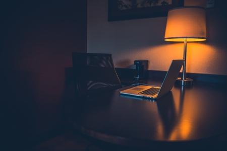 밤 업무용 책상. 노트북 및 야간 조명 어두운 고요한 테마. 나무 바탕 화면.