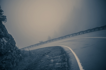 road conditions: Foggy Curved Road. Dangerous Mountain Road. Bluish Color Grading.