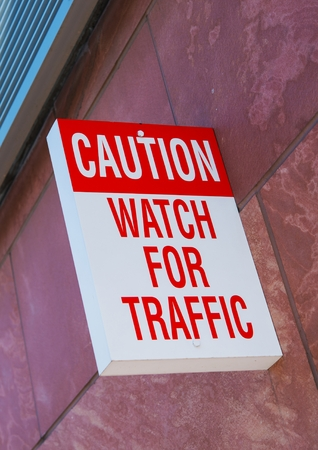 backlite: Caution, Watch For Traffic Wall Sign. Warning Sign Stock Photo