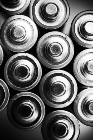 power industry: Energy Inside the Batteries. Mobile Power Industry Concept. AA Batteries From the Top. Vertical Black and White Photo