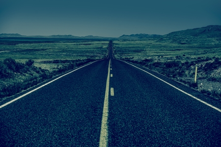 bluish: Down the Road. Straight Desert Highway in Bluish Color Grading. Straight Road to Nowhere.