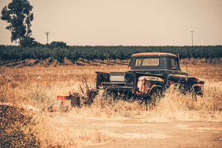 jalopy: Junk Aged Pickup on the Dry California Meadow. History of American Transportation. Stock Photo