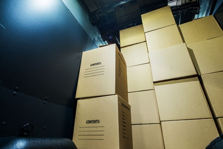 reloading: Pile of Boxes in a Cargo Van Closeup. Products Transportation Industry. Shipping and Delivery.