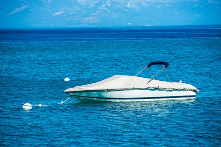recreational boat: Small Motorboat on the Clear Blue Lake Water. Recreational Boating Theme.