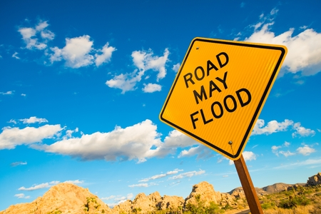 flood area: Road May Flood Warning Sign in California Flash Flood Desert Area.