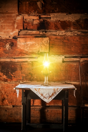log cabin: Burning Oil Lamp on the Aged Wooden Table in the Vintage Cabin Scenery.
