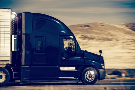 Speeding Dark Blue Semi Truck in Nevada, United States. Trucking in Western USA. Stock Photo