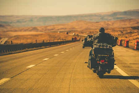 Biker Riding Motorcycle on the Nevada HIghway, USA. Motorbiking Theme.