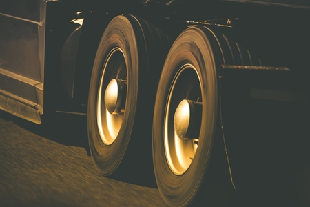 tire: Spinning Semi Truck Wheels Closeup Photo. Browny Color Grading. Trucking and Transportation Theme.