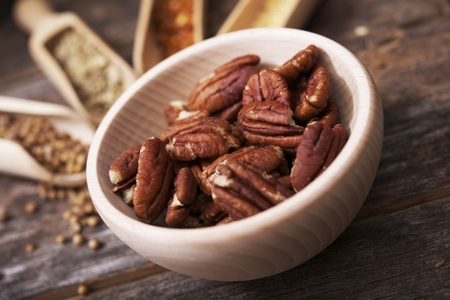 pecans: Pecans in the Small Wooden Bowl with Other Spices in the Background. Stock Photo