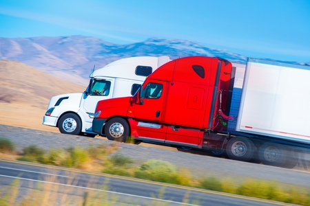 delivery truck: Two Speeding Semi Trucks on the Nevada Highway, USA. Trucking in America.