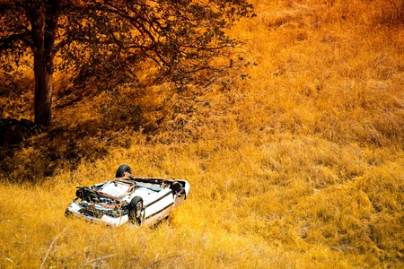 Rollover Compact Car Crash. White Crashed Car in the Mountain Road Ditch in California, USA. Traffic Accident. 스톡 콘텐츠