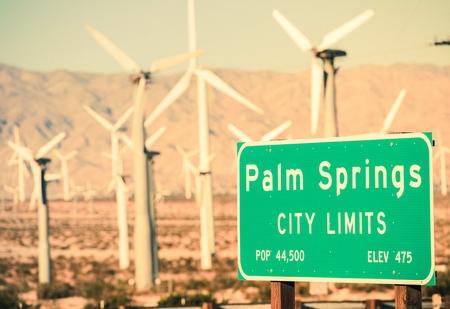 パーム ・ スプリングス ・ シティ高速道路標識と、バック グラウンドでの風力タービンを制限します。パーム ・ スプリングス、カリフォルニア、 写真素材