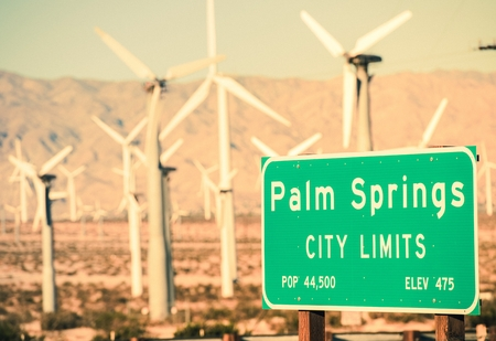 Palm Springs City Limits Highway Sign and Wind Turbines in the Background. Palm Springs, California, USA. Stock Photo