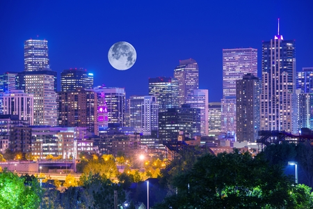Denver Colorado at Night. Denver Downtown Skyline and the Full Moon on Clear Sky. Stock Photo