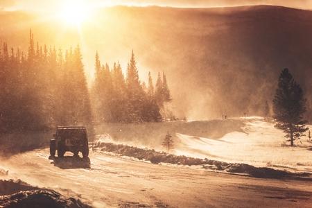 conduciendo: Extreme Condition invierno Road. Colorado Mountain Road y la tormenta del invierno con viento fuerte. Todos SUV ruedas motrices en el camino helado cubierto por la nieve. Foto de archivo