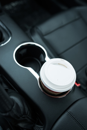go inside: Coffee Drinking While Driving. Single Paper Coffee Cup Inside Car Cup Holder.