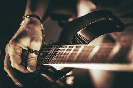 기타리스트 연극. 일렉트릭 기타 연주 근접 사진입니다. 록맨 기타 플레이어 음악 테마입니다.