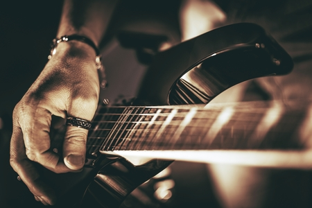 Guitarist Plays. Electric Guitar Playing Closeup Photo. Rockman Guitar Player Music Theme.