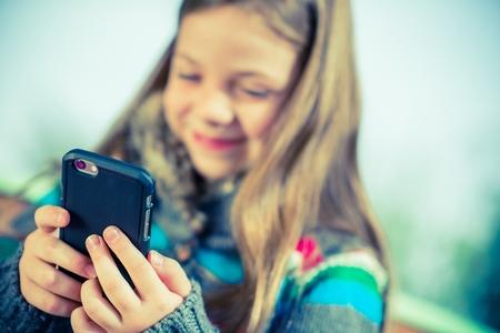 Happy Teenage Girl Playing With Smartphone. Young Girl Using Modern Smartphone. Stock fotó