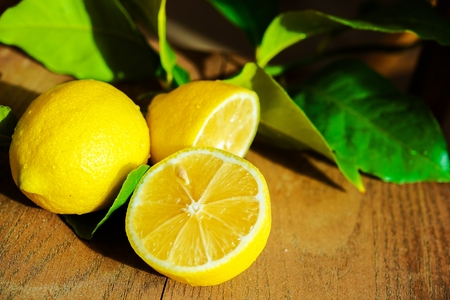 lemon tree: Fresh Sliced Lemon and Lemon Tree Leaves on Wooden Table.