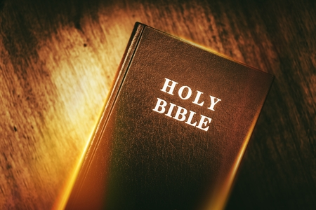 Holy Bible in Dark Browny Vintage Color Grading. Glowing Light Holy Bible Stock Photo