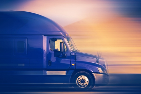 shipper: Rush Trucking. Speeding Blue Semi Truck on the American Highway. Trucking Concept.