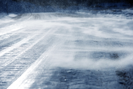 icy conditions: Icy Road with Drifting Snow Closeup. Dangerous Icy Road Conditions.