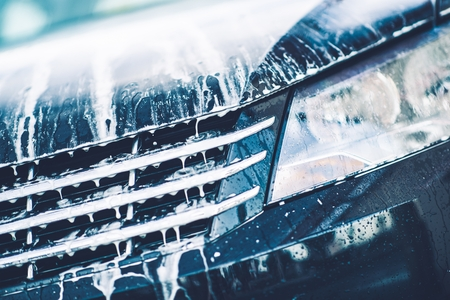 Car Foaming Closeup. Car Active Foam Cleaning Theme.