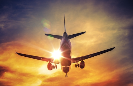 airplane wing: Landing Airplane and the Sun. Air Travel and Transportation Photography Concept. Stock Photo
