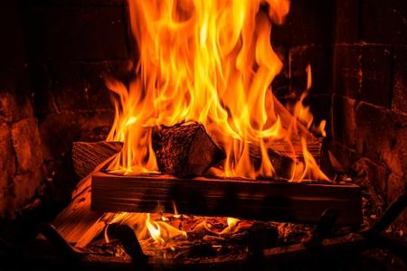 cabaña: Registros ardientes de madera en una chimenea de ladrillo de la vendimia.