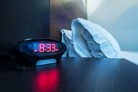 Hotel Room Alarm Clock. Waking Up in a Hotel Photo Concept. Business Travels.