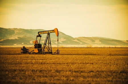 Aged Oil Pump on Colorado Prairie with Mountain Hills . Oil Industry Theme. Stock Photo