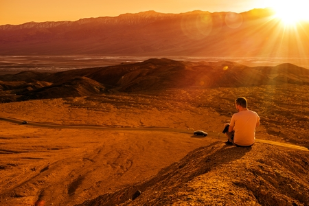 Death Valley Private Vista. Young Tourist on the Sandy Hill Enjoying the Sunset. Death Valley, California, United States.