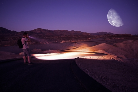 Hiker with Powerful Flashlight on Death Valley Trail During Starry Night. Night in Death Valley National Park, California, United States.