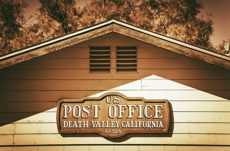 post office: United States Post Office Death Valley. Post Office Building Wooden Sign. Vintage Color Grading. Stock Photo