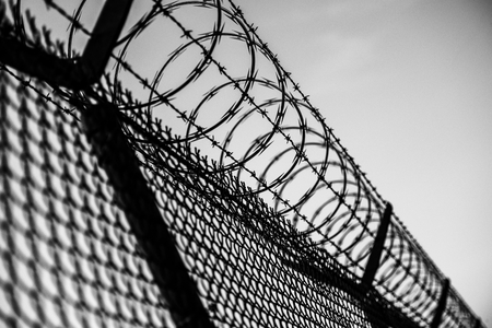 criminals: Prison Fence in Black and White. Barbed Wire Fence Closeup.