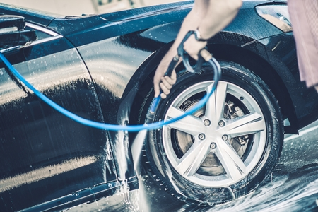 soaping: Self Car Washing. Cleaning Wheels Using High Pressure Water. Stock Photo