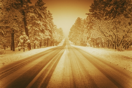 driving conditions: Scenic Winer Road in Sepia. Winter Driving Conditions. Forest Road. Stock Photo