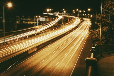 highway lights: American Highways System at Night. Traffic in Motion. Long Exposure Photo. Dark Sepia Color Grading.