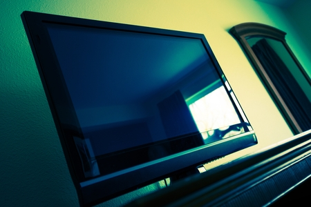 greenish blue: Flat Screen TV in a Room. Television Device. Dark Greenish Blue Color Grading. Stock Photo